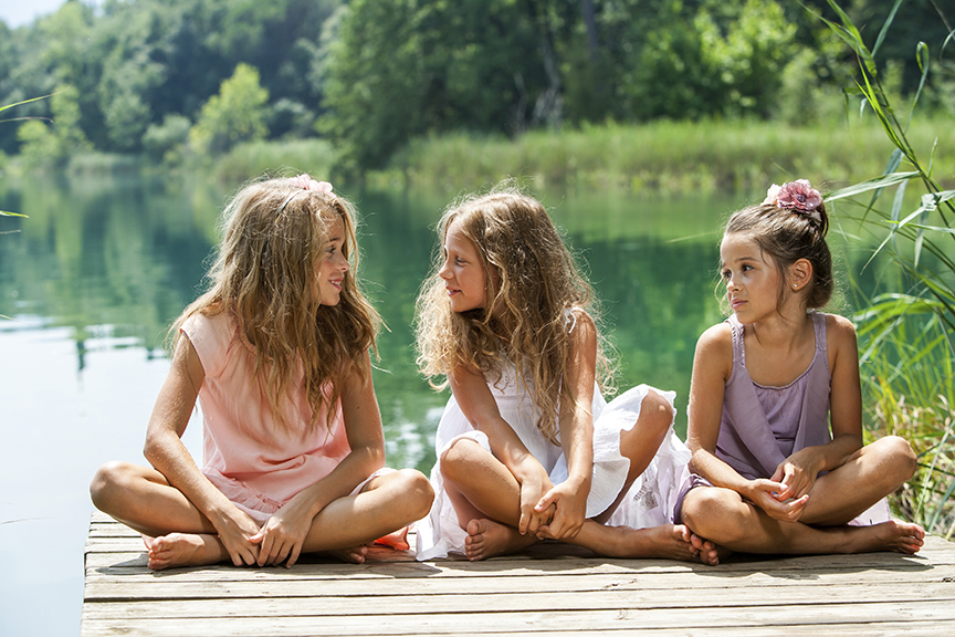 Three girl friends sitting on a deck at lake Conroe.